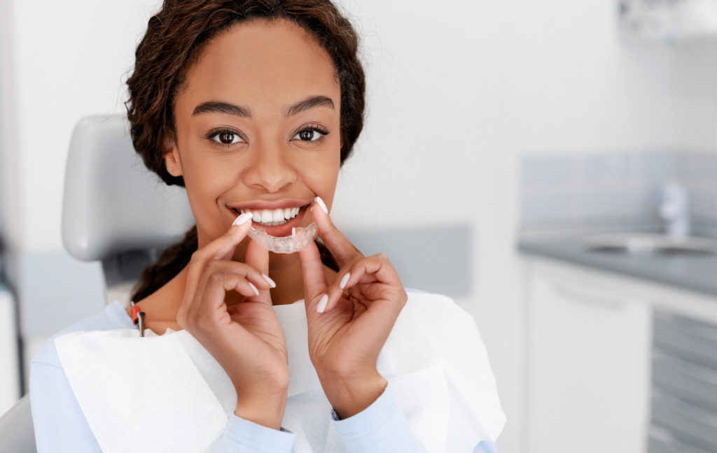 Dental Treatment Concept. Close up of young black woman holding invisalign braces.
